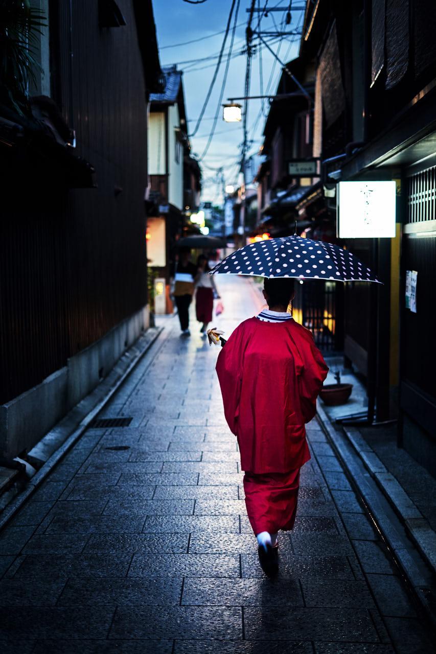 Une femme en kimono marche sous la pluie