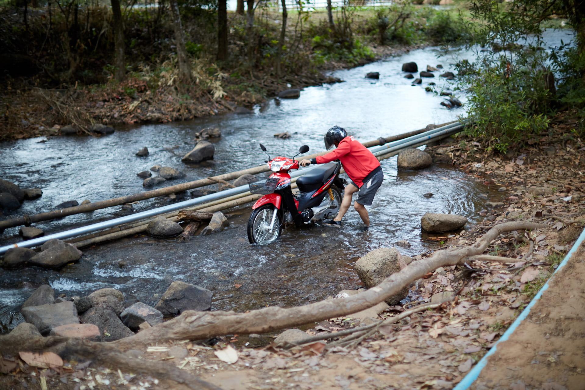 Un homme lave son scooter dans une rivière