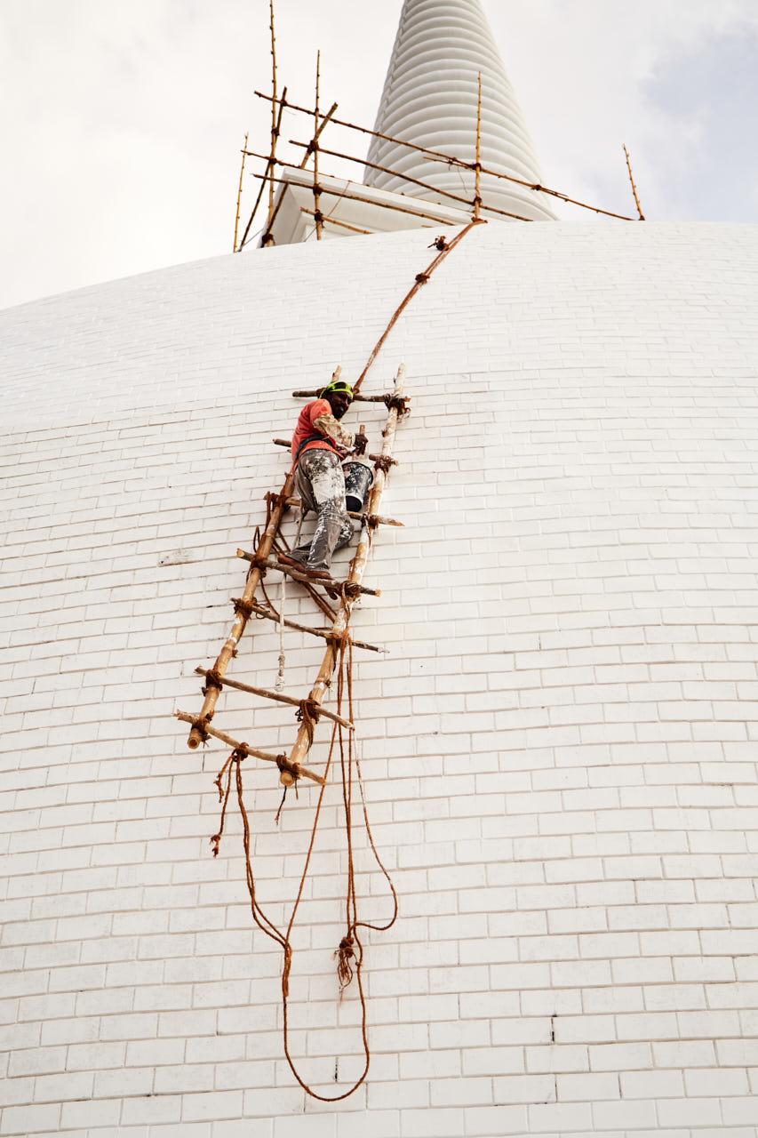 Un homme repeint une pagode